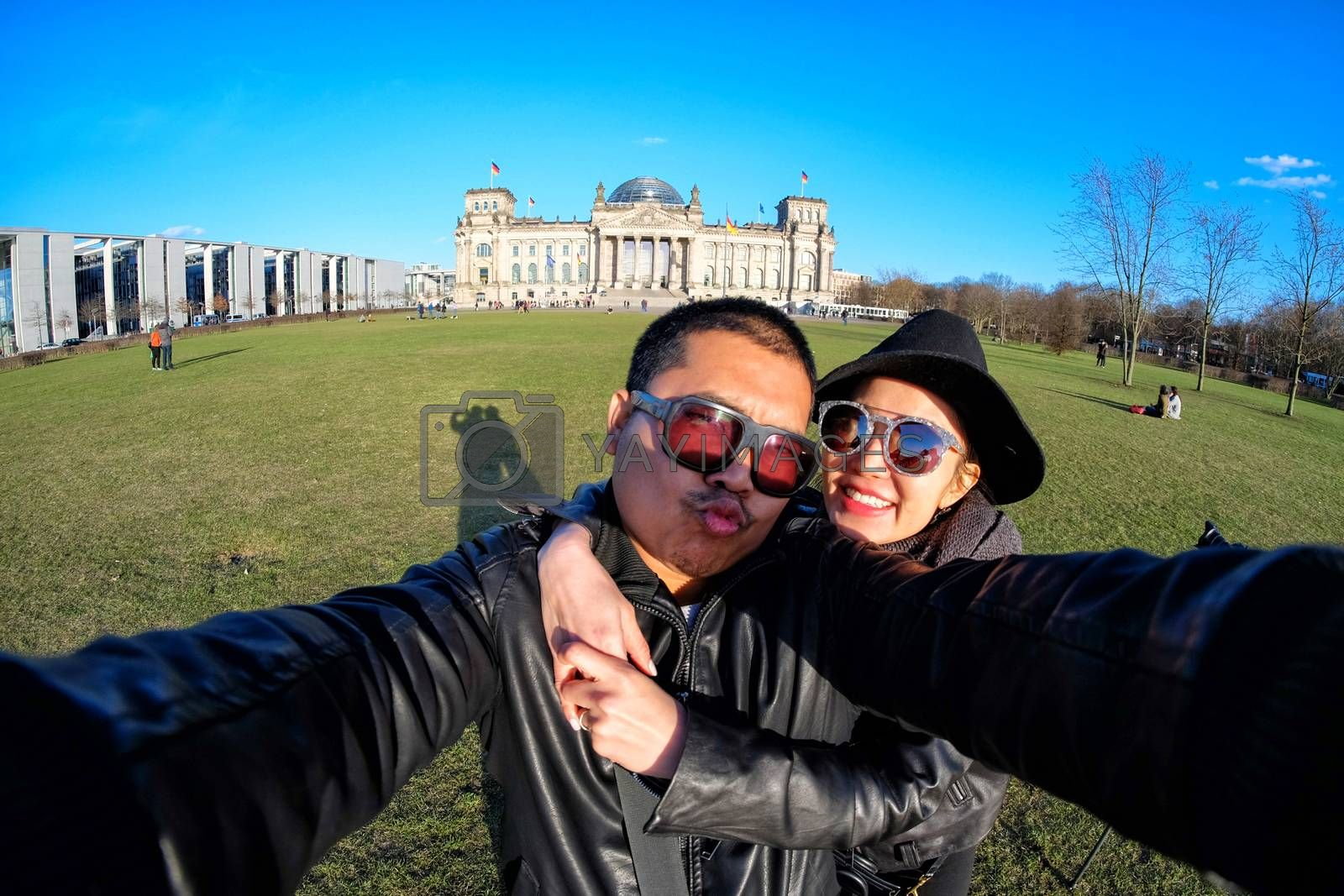 Young Couple Tourists selfie with mobile phone near the Reichstag building (german government) in Berlin, Germany
