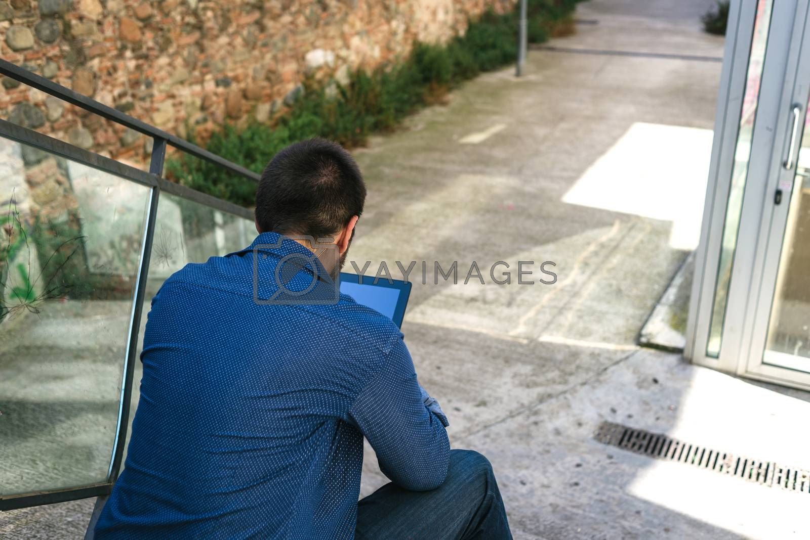 Portrait of a bearded man sitting on steps while using a tablet
