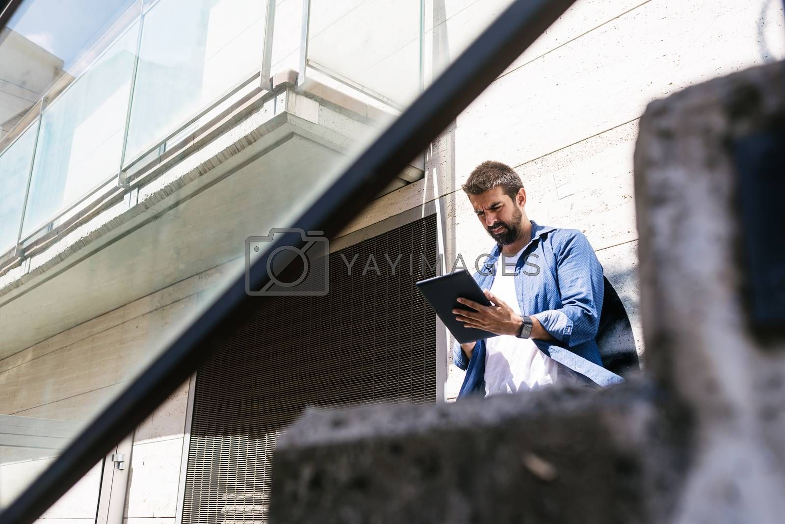 Bearded man sitting on steps while using a tablet by raferto1973