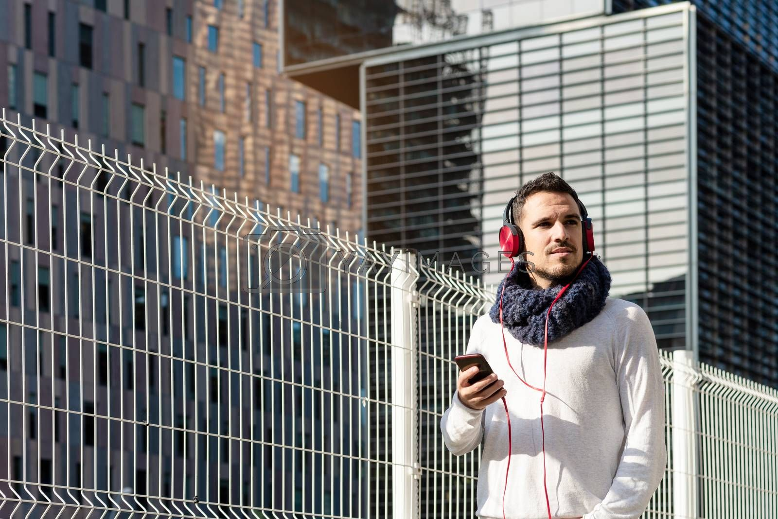 Young bearded male with headphones and holding smartphone while walking against skyscrapers in sunny day