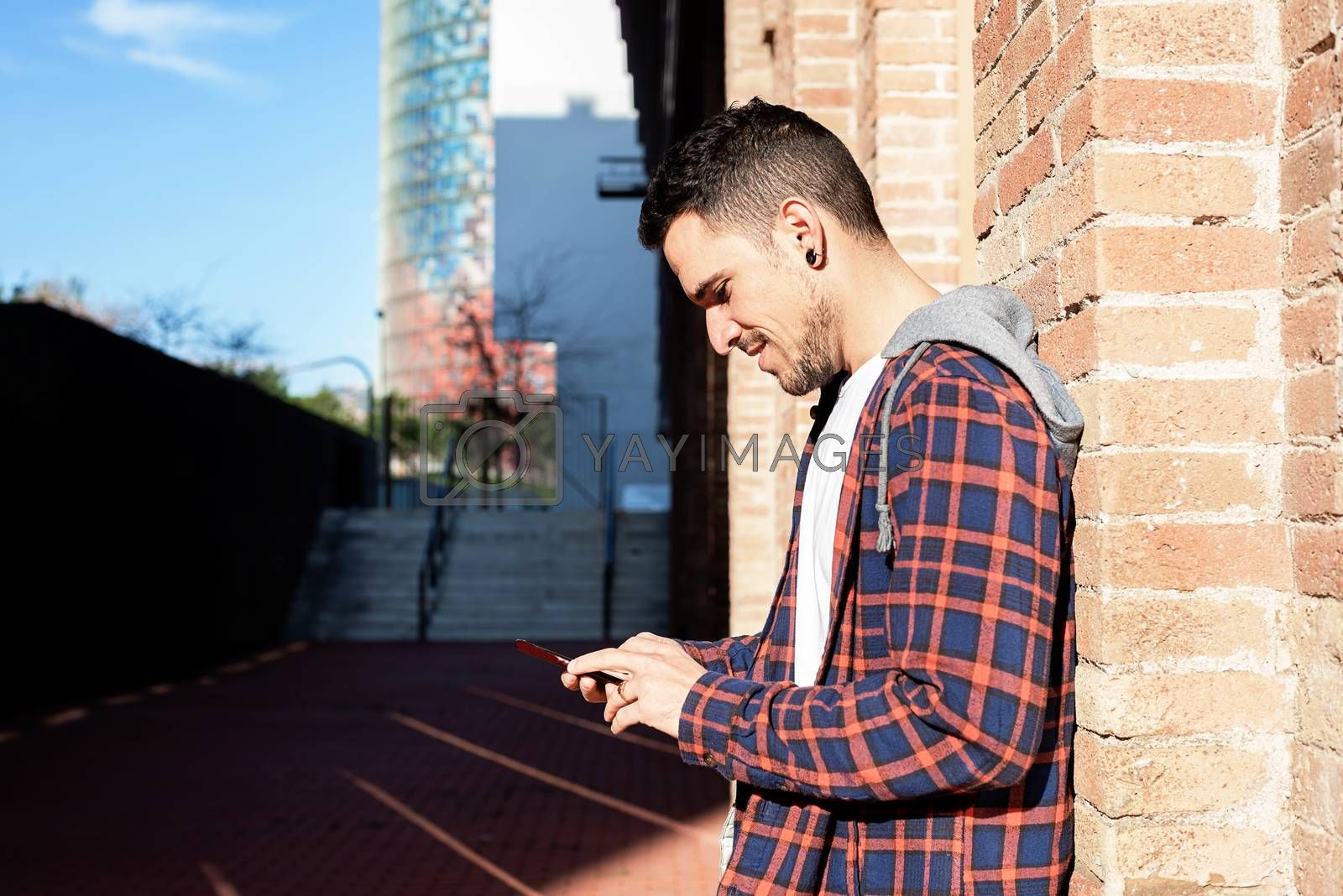 Young bearded man leaning on a bricked wall while using a smartphone