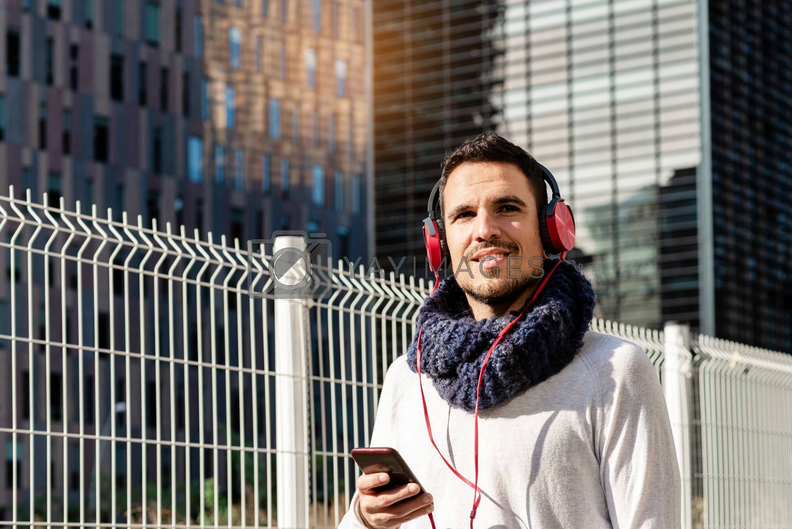 Young bearded male with headphones and holding smartphone while walking against skyscrapers in sunny day by raferto1973