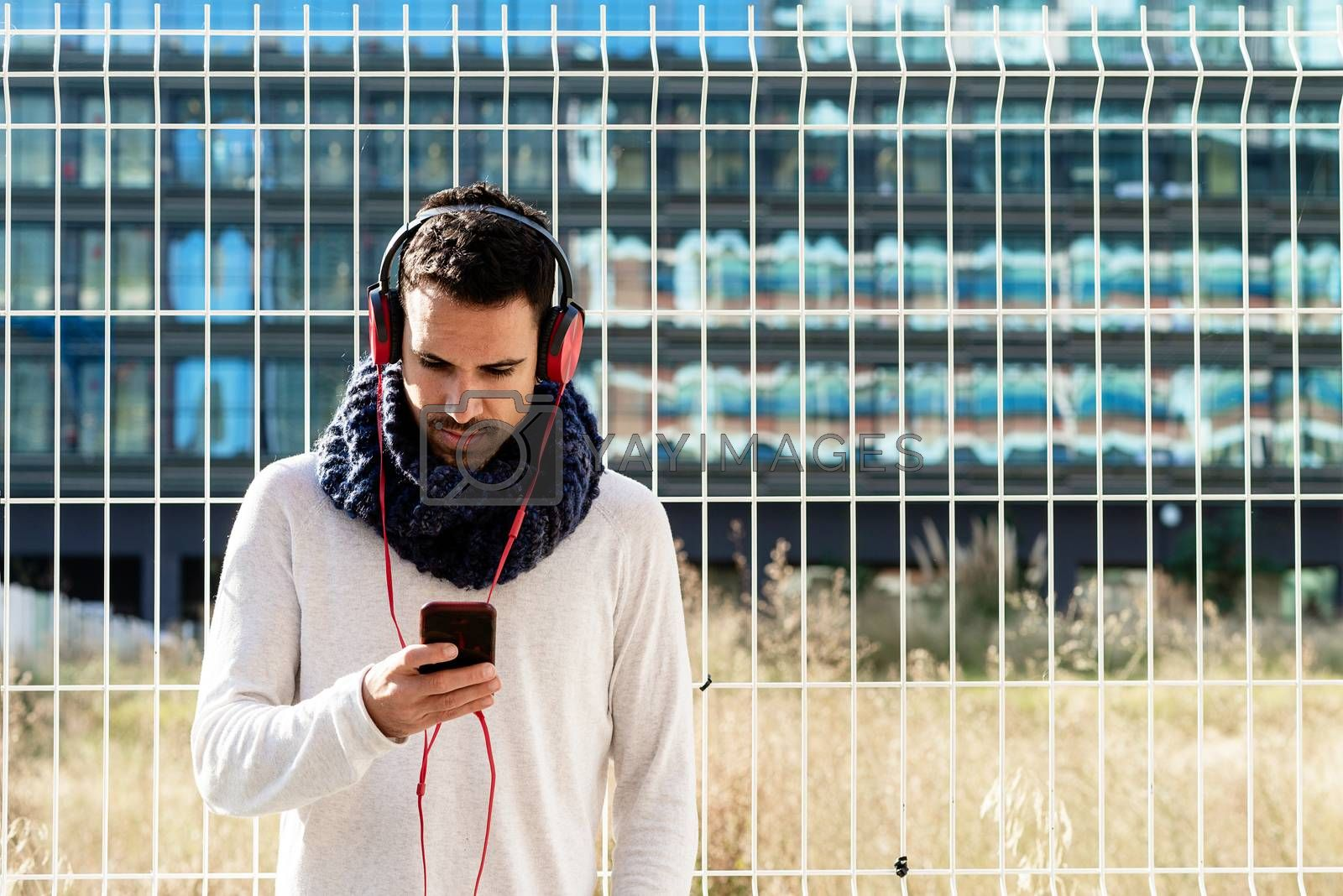 Young bearded male with headphones and holding smartphone while leaning on a metallic fence against skyscrapers in sunny day by raferto1973