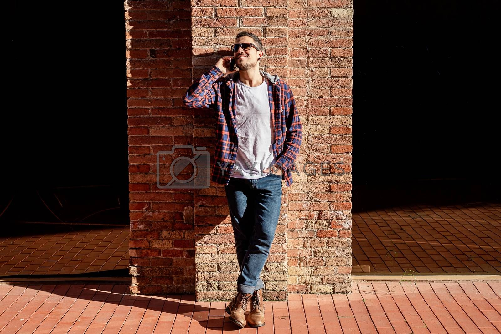 Young bearded man leaning on a bricked wall wearing sunglasses while using a smartphone outdoors. by raferto1973