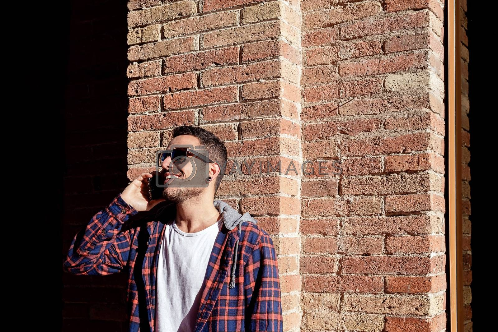 Young bearded man leaning on a bricked wall wearing sunglasses w by raferto1973