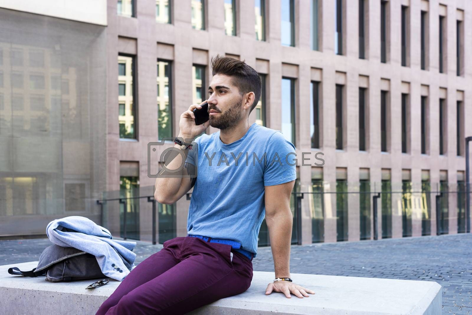 Young businessman talking on his phone outdoors by raferto1973