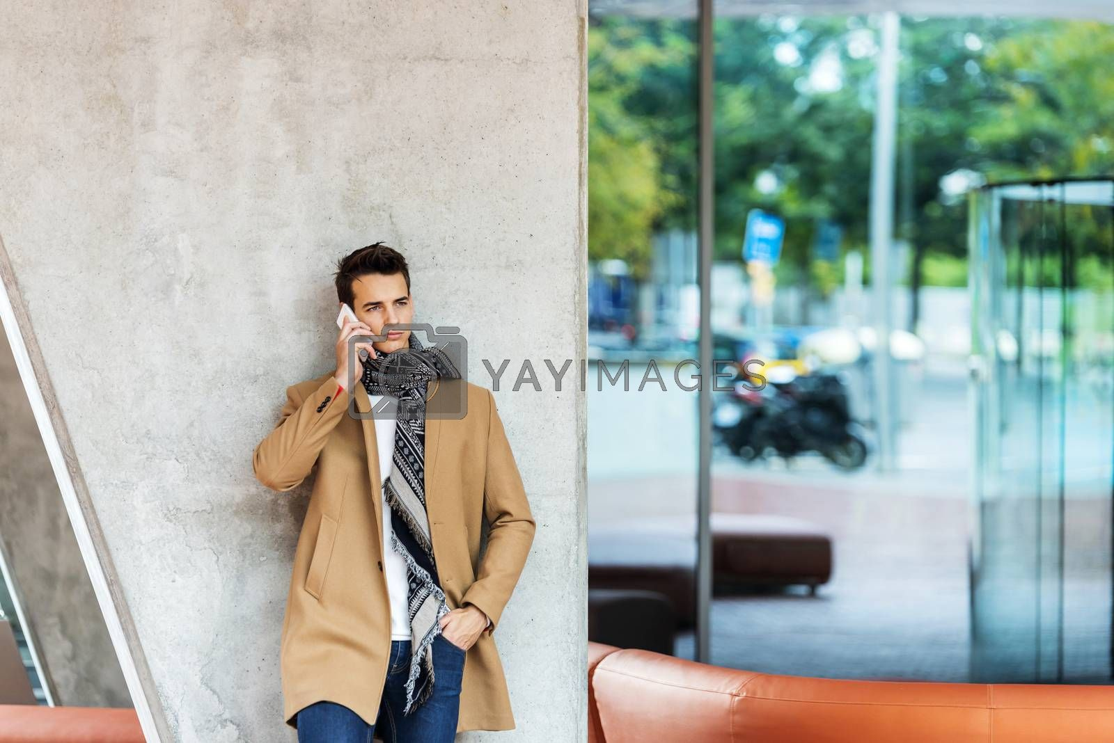Front view of fashionable young man wearing denim clothes leaning on a wall while using a mobile phone outdoors