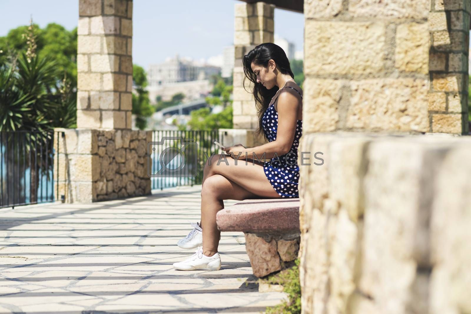 Beautiful woman in blue dress sitting on a bench while using a smartphone