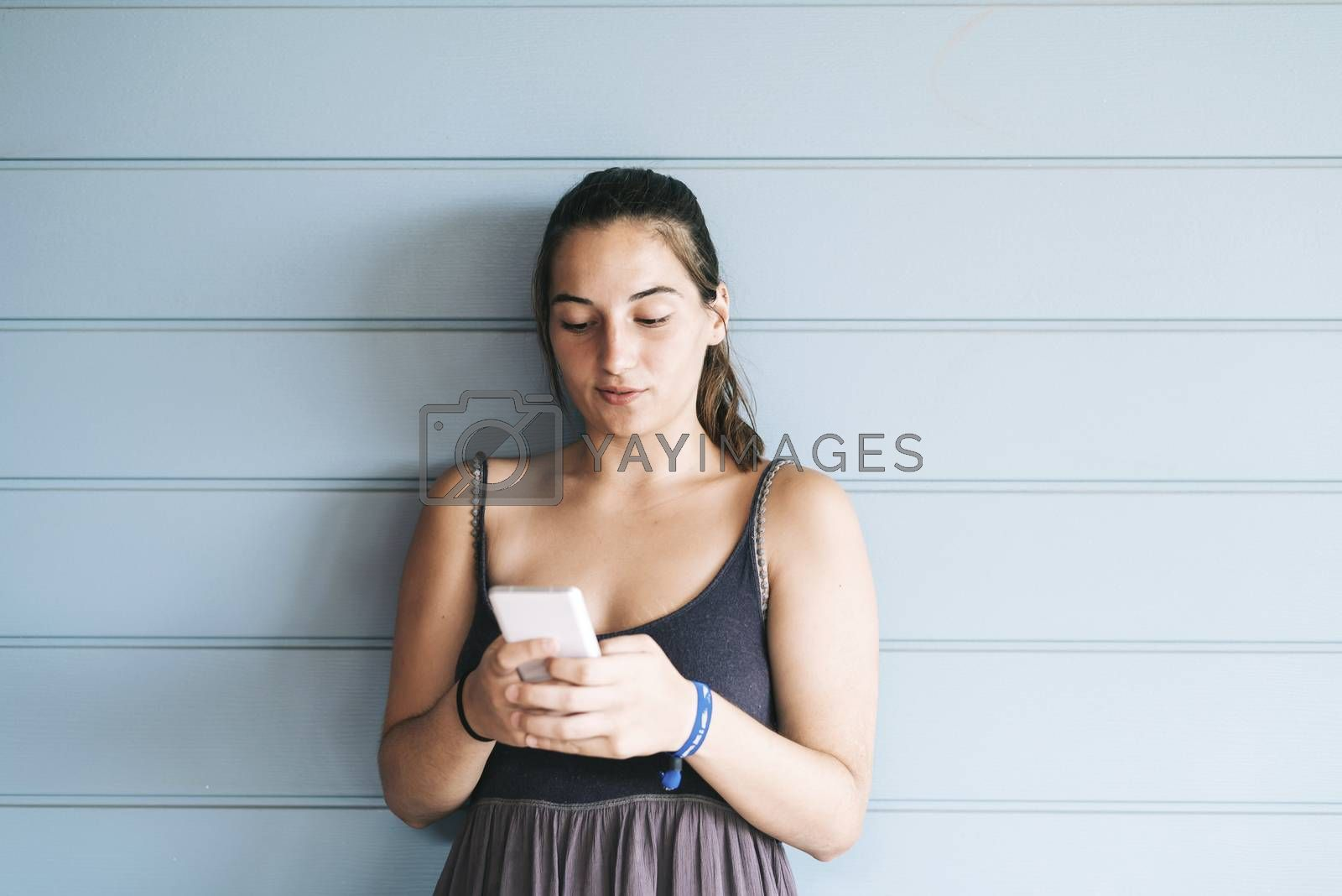Beautiful woman leaning on a wood wall while using a smartphone