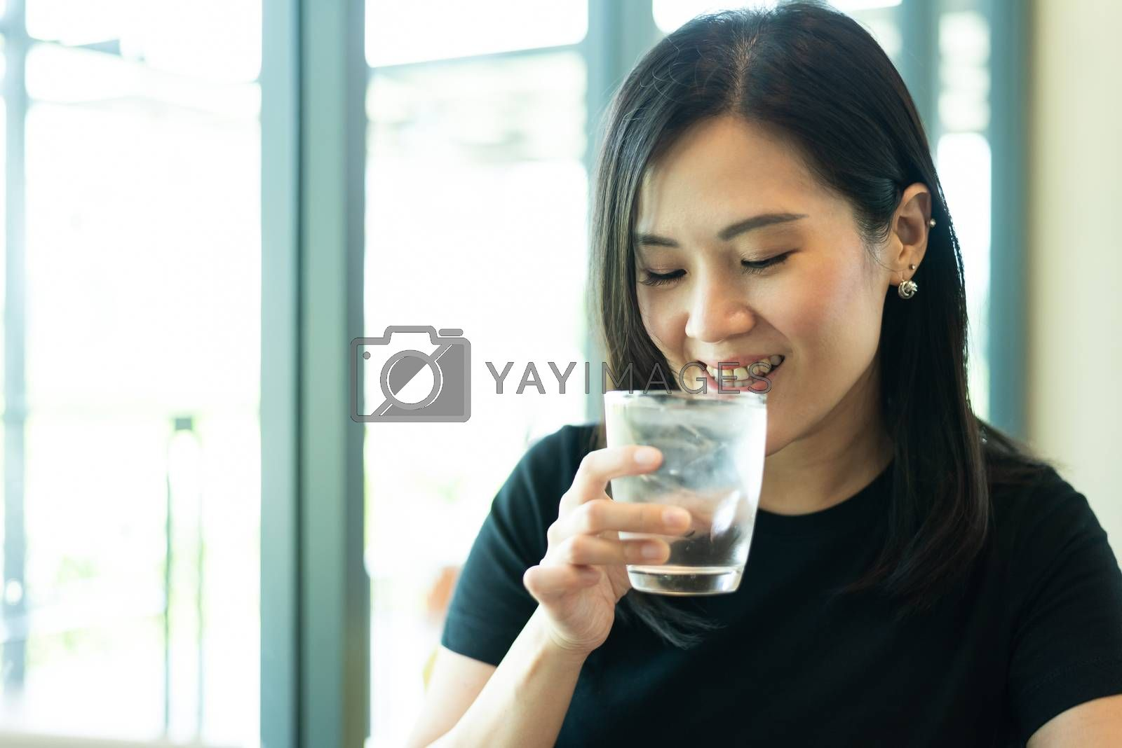 An Asian beautiful woman has drinking a water in the morning.