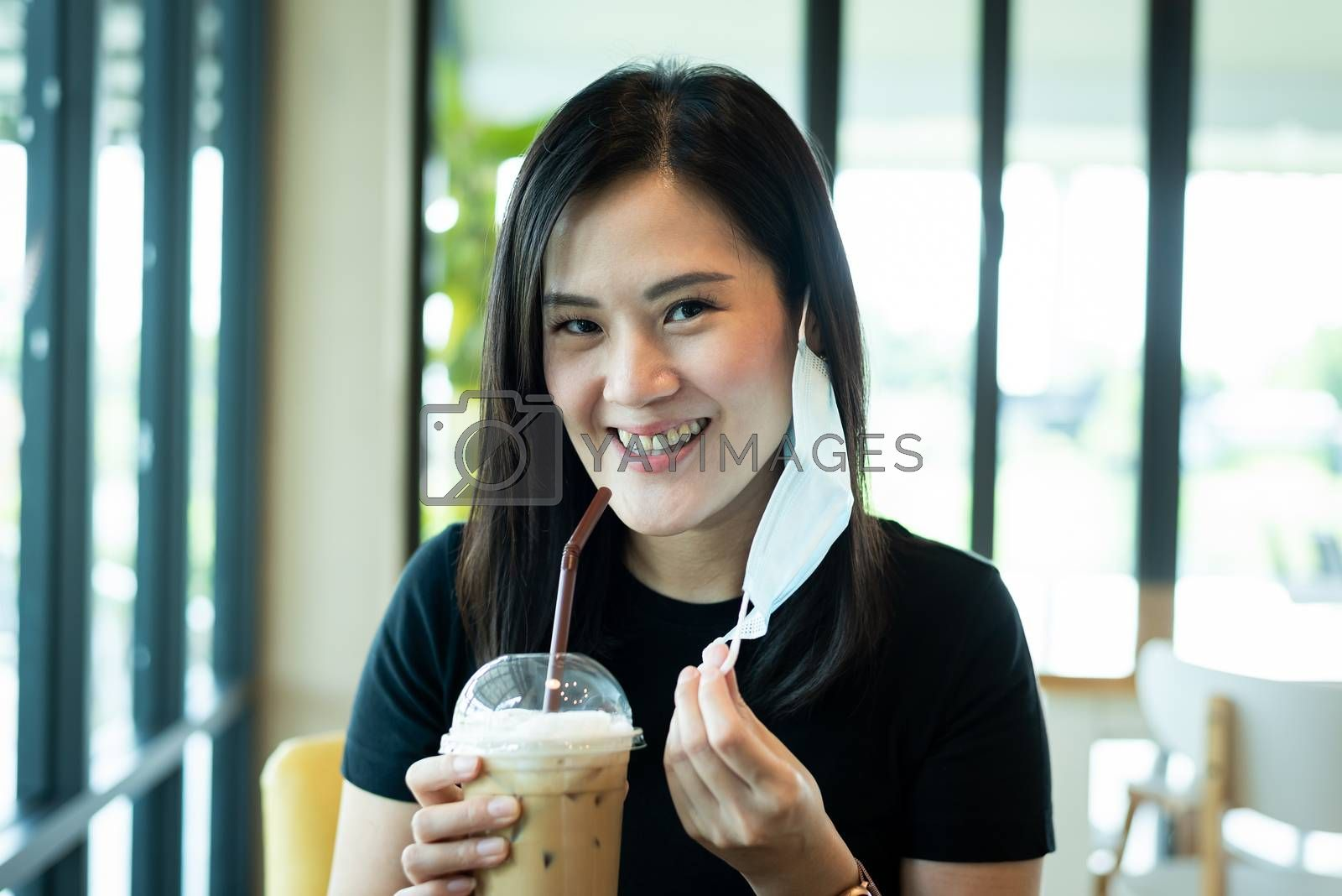 An Asian beautiful woman has to remove a blue mask and drinking an iced cappuccino with happiness in the morning.