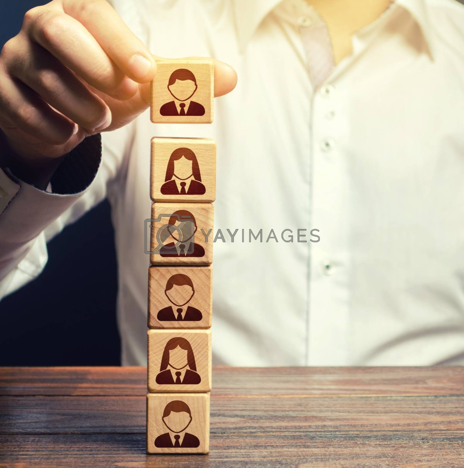 Business leader builds a people block tower. Definition of people in a hierarchical system. Meritocracy. Company organization. Hiring, recruiting workers. Leadership skills, team personnel management.