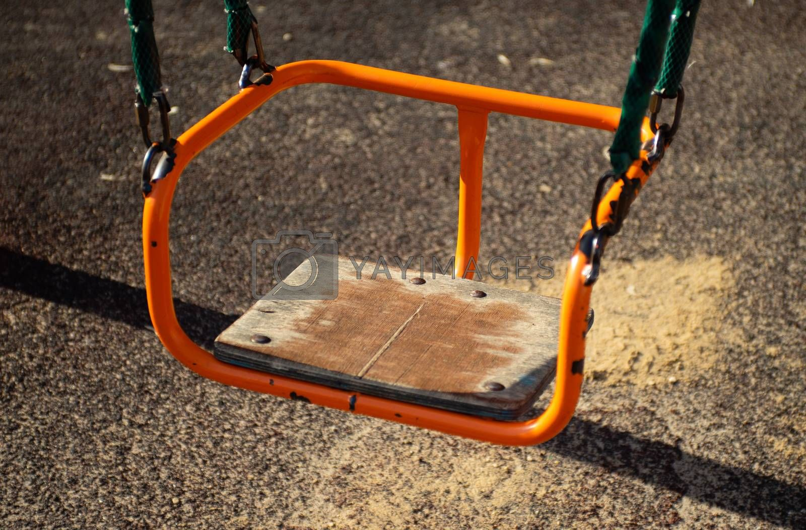 An empty old orange swing on a Playground on a summer evening.