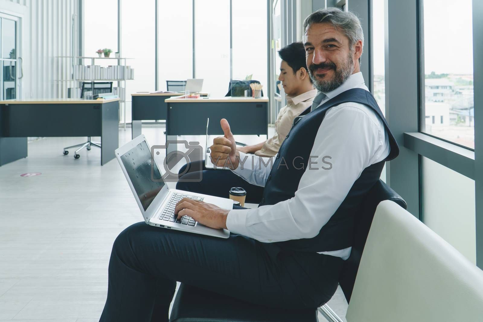 group of businessmen using laptops and drinks coffee before a business meeting. Asian young men and Adult male Caucasian people talking while awaiting an interview. social distancing is new normal