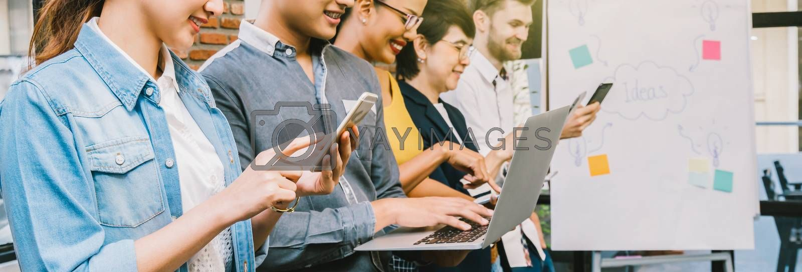 Banner and web page or cover template of Group Of Asian and Multiethnic Business people with casual suit using the technology mobile, tablet, laptop and computer for working in modern Office