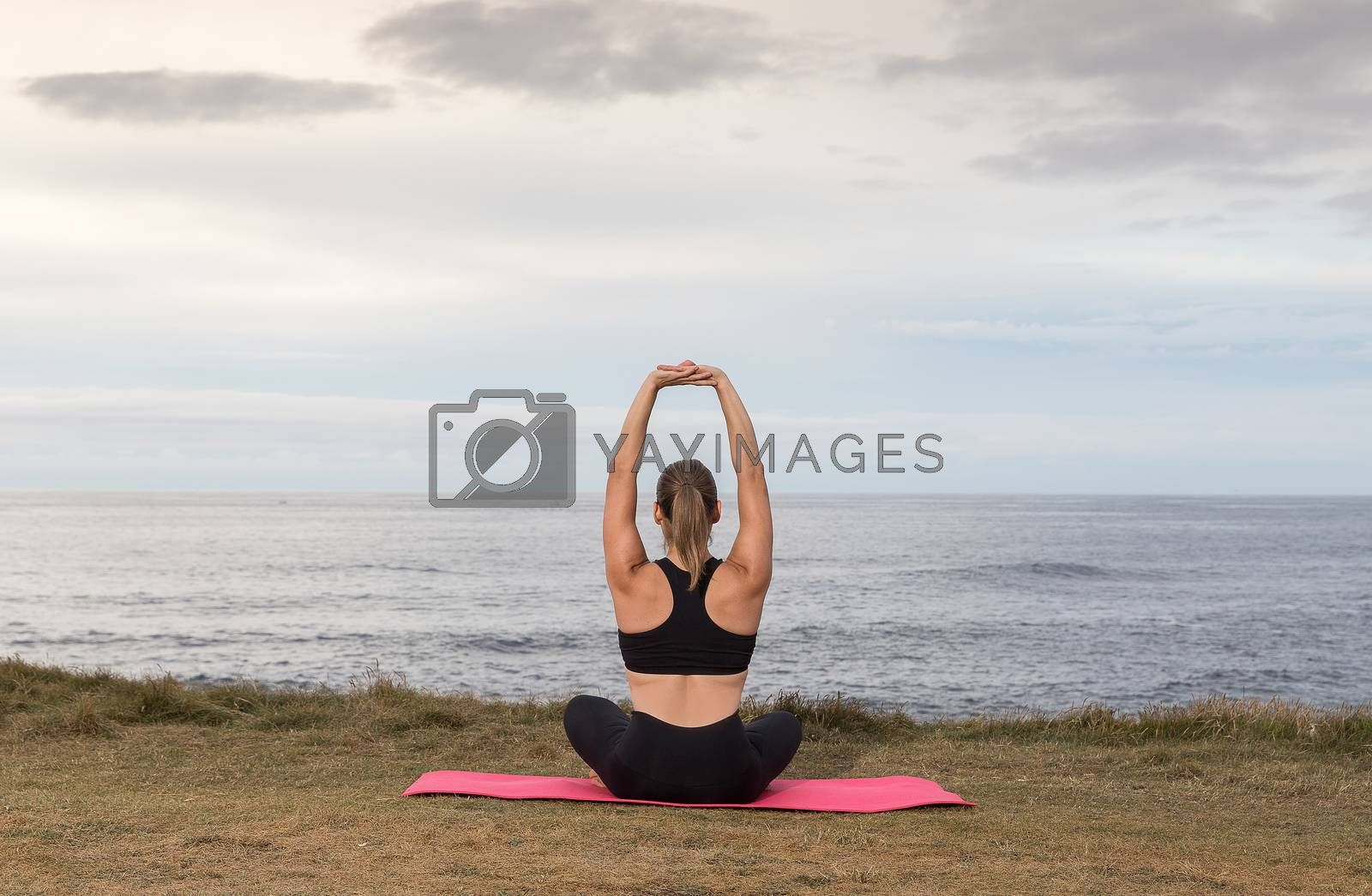 Woman in black sportswear exercising outdoors on a pink mat with the sea in the background.