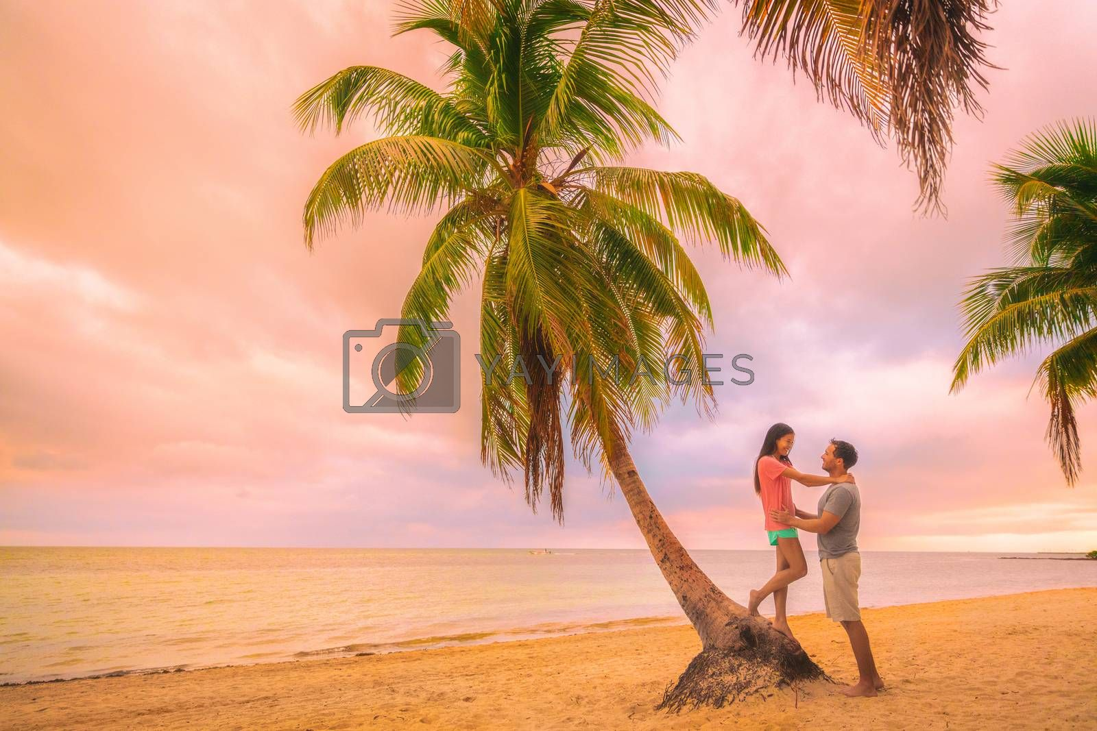 Romantic sunset stroll young couple in love embracing on palm trees at pink dusk clouds sky. Romance on summer travel vacation.
