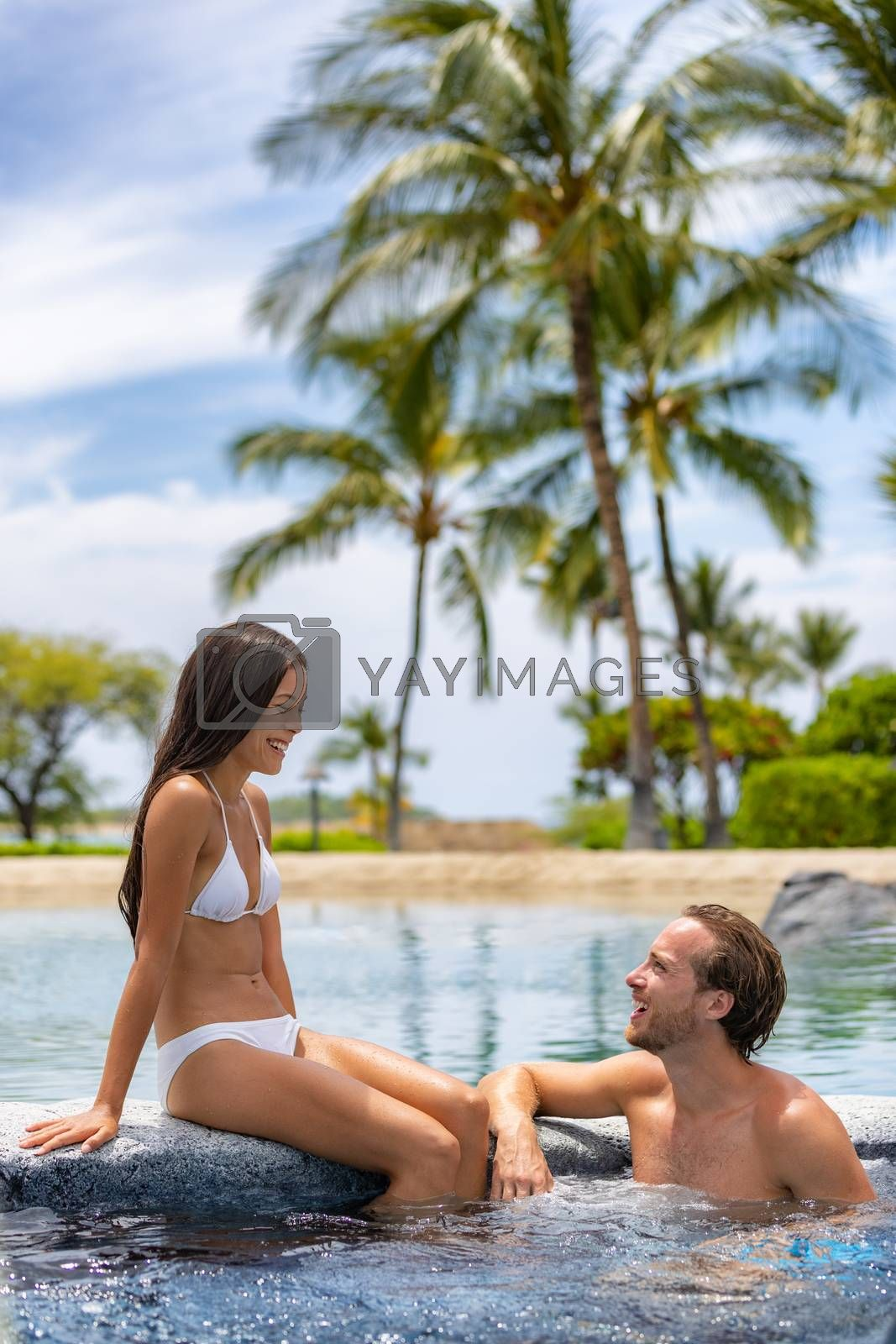 Spa resort couple relaxing enjoying jacuzzi hot tub swimming pool outdoors on summer vacation travel holidays honeymoon getaway. Young interracial couple laughing happy, Asian woman, Caucasian man.