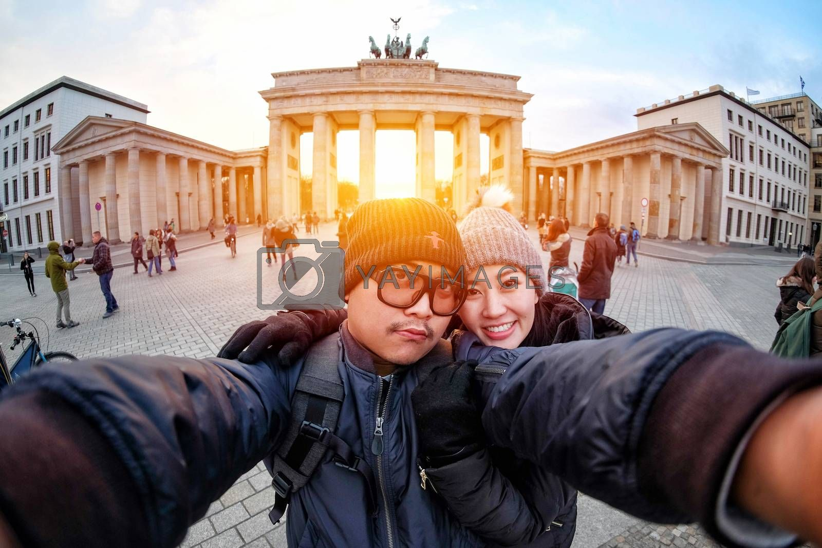 Young Couple Tourists selfie with smartphone at Brandenburger Gate in sunlight, the famous landmark of berlin, germany