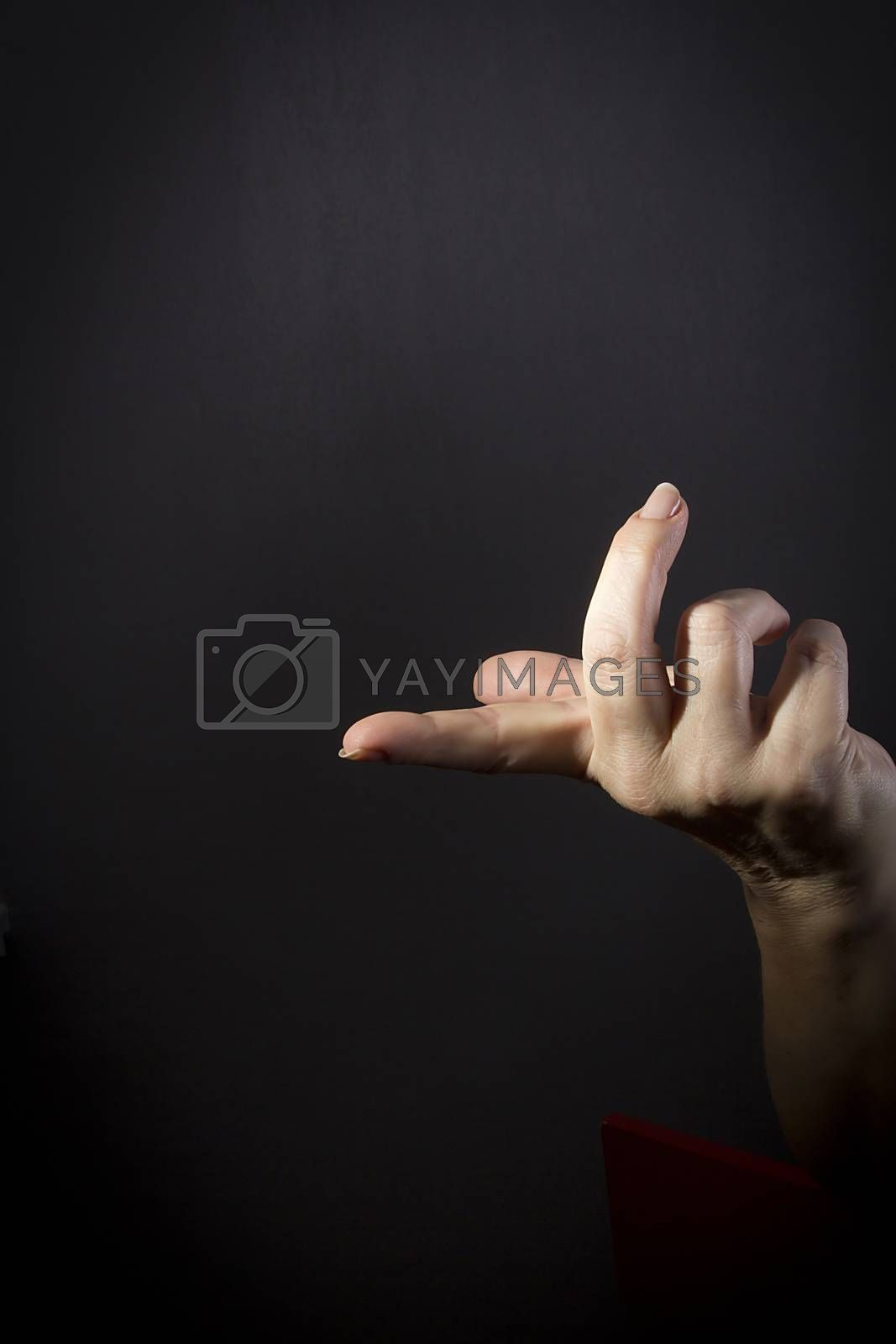 Female hand with protruding forefinger on black background