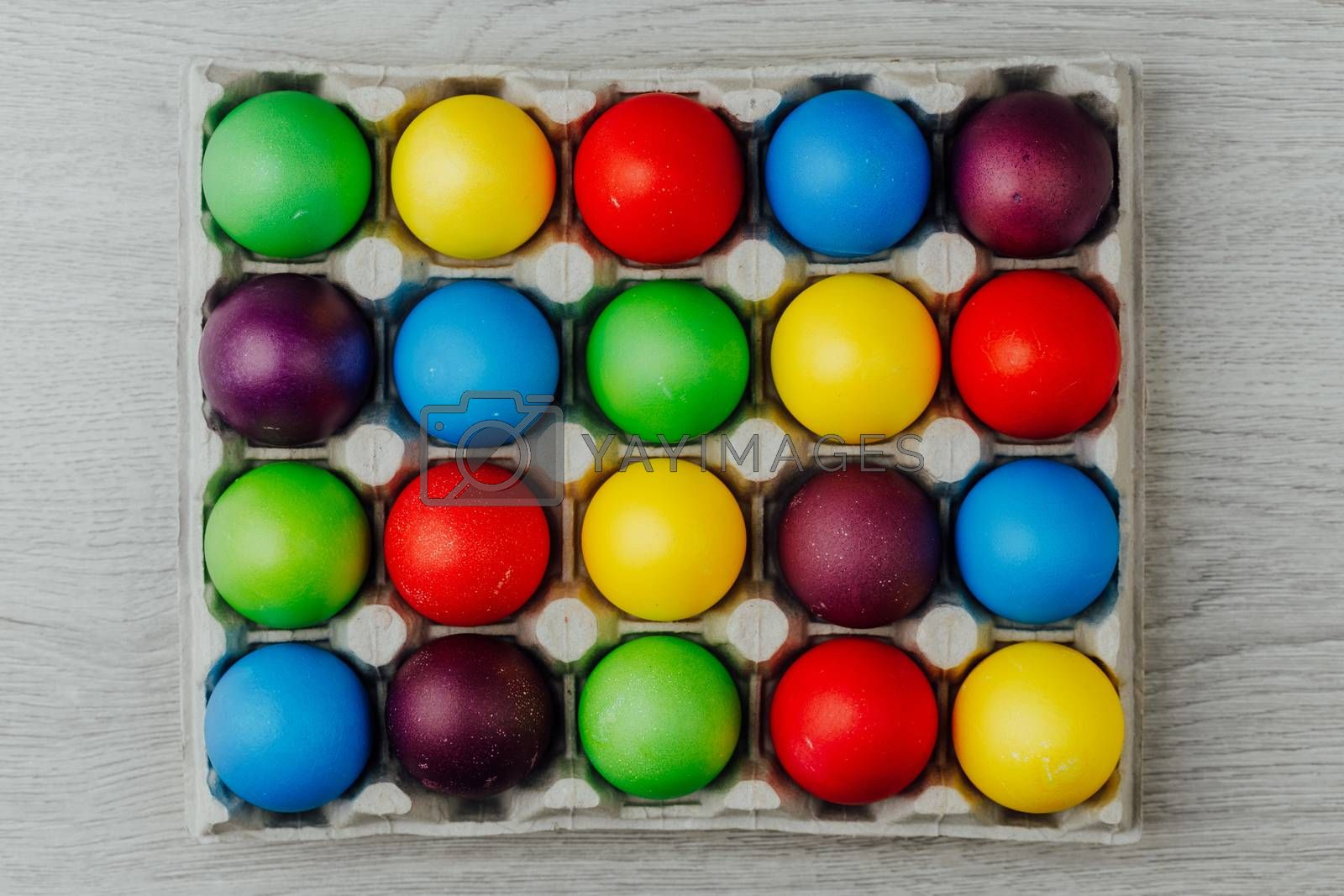 Easter festive multicolor eggs carton, light gray wooden background, top view
