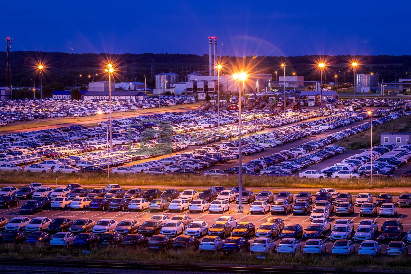 Volkswagen, Russia, Kaluga - AUGUST 26, 2020: New cars parked at distribution center of automobile factory at night with lights. Parking on the open air.