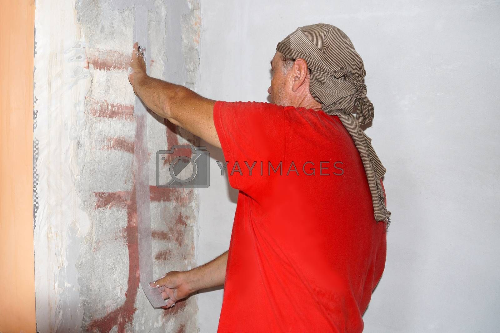 a man gluing a reinforcing tape to a crack in a wall.