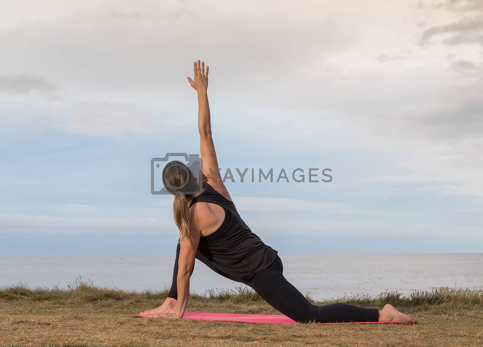 Woman in sportswear stretching outdoors on a pink mat with the sea in the background.