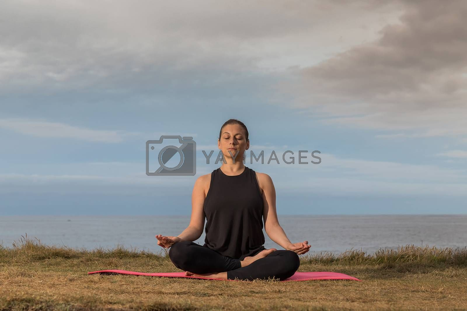 Woman in sportswear doing yoga outdoors on a pink mat with the sea in the background.