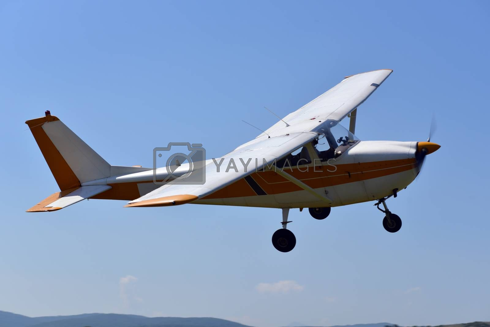 Royalty free image of A small sports single-engine plane is flying by aselsa