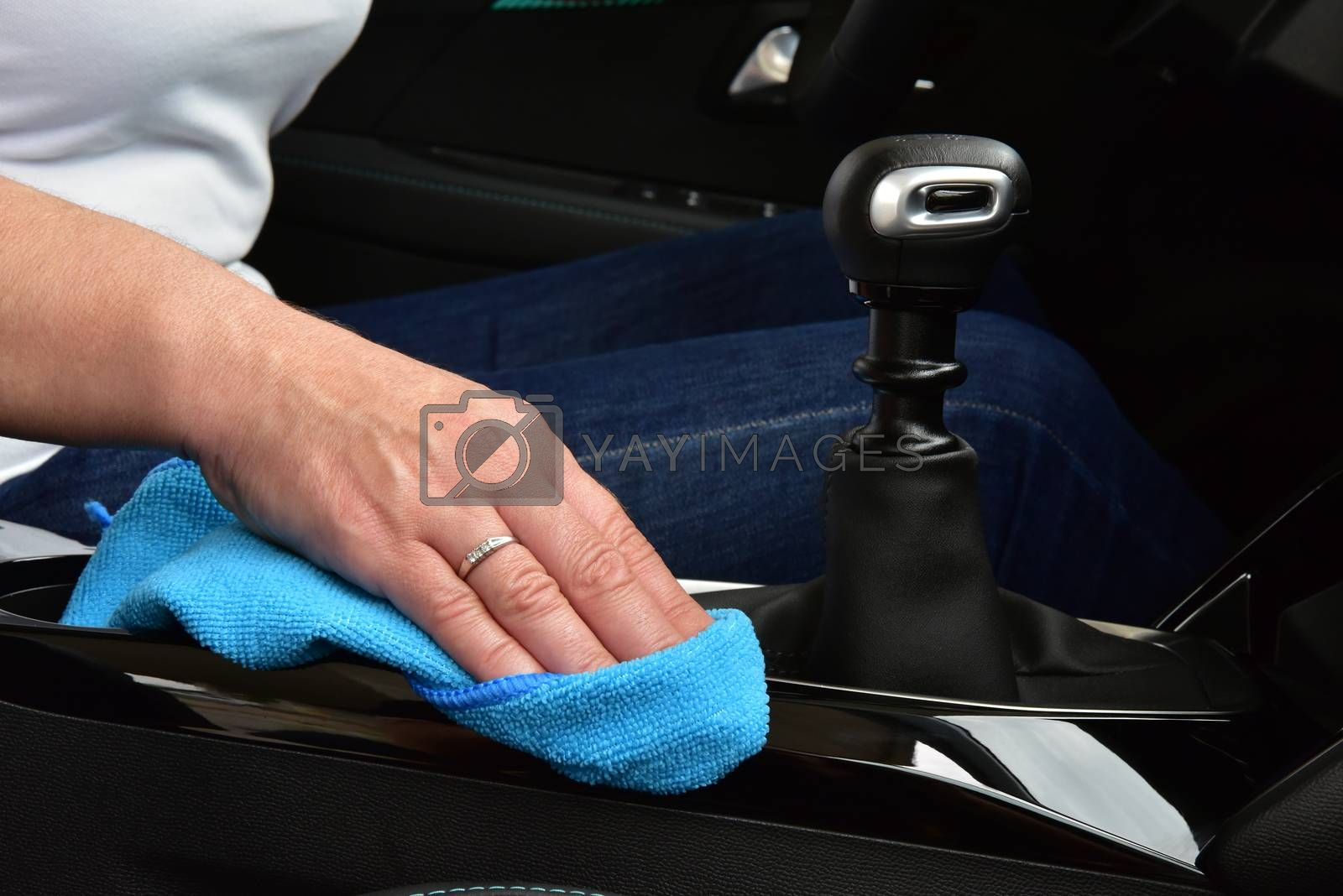 Royalty free image of Cleaning the car console with a microfiber cloth by aselsa