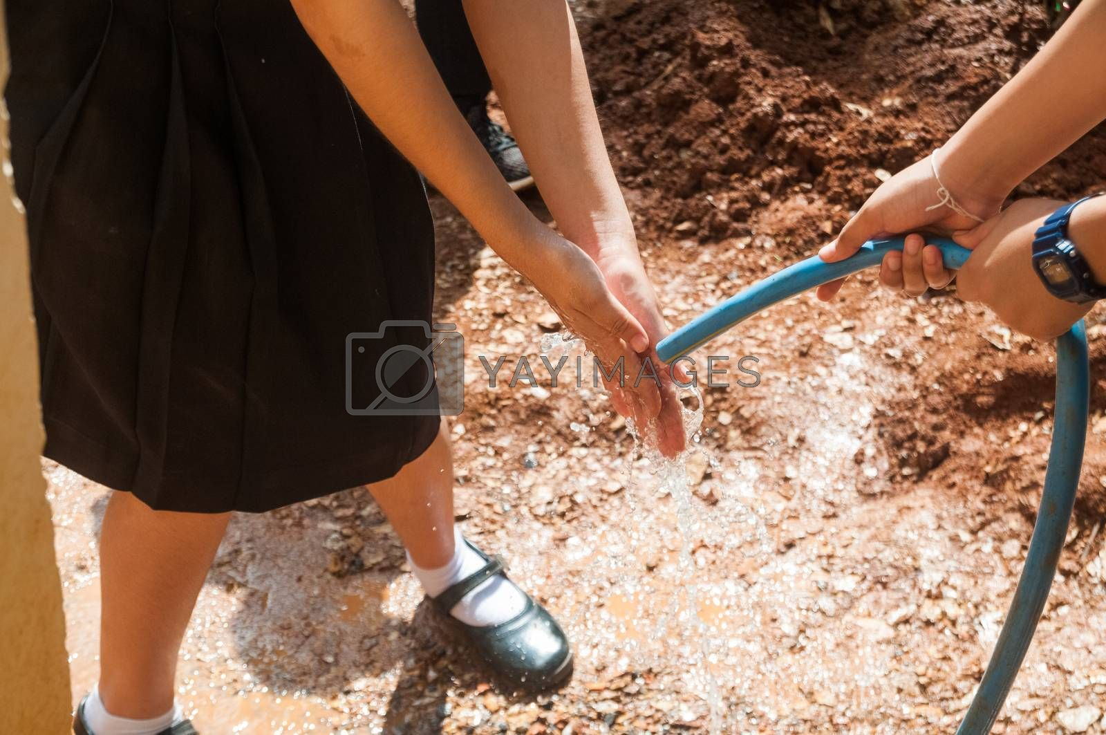 Student holding garden hose spraying fresh water from rubber tube to wash hands stained after plant a tree as outdoor activity to save environment and earth