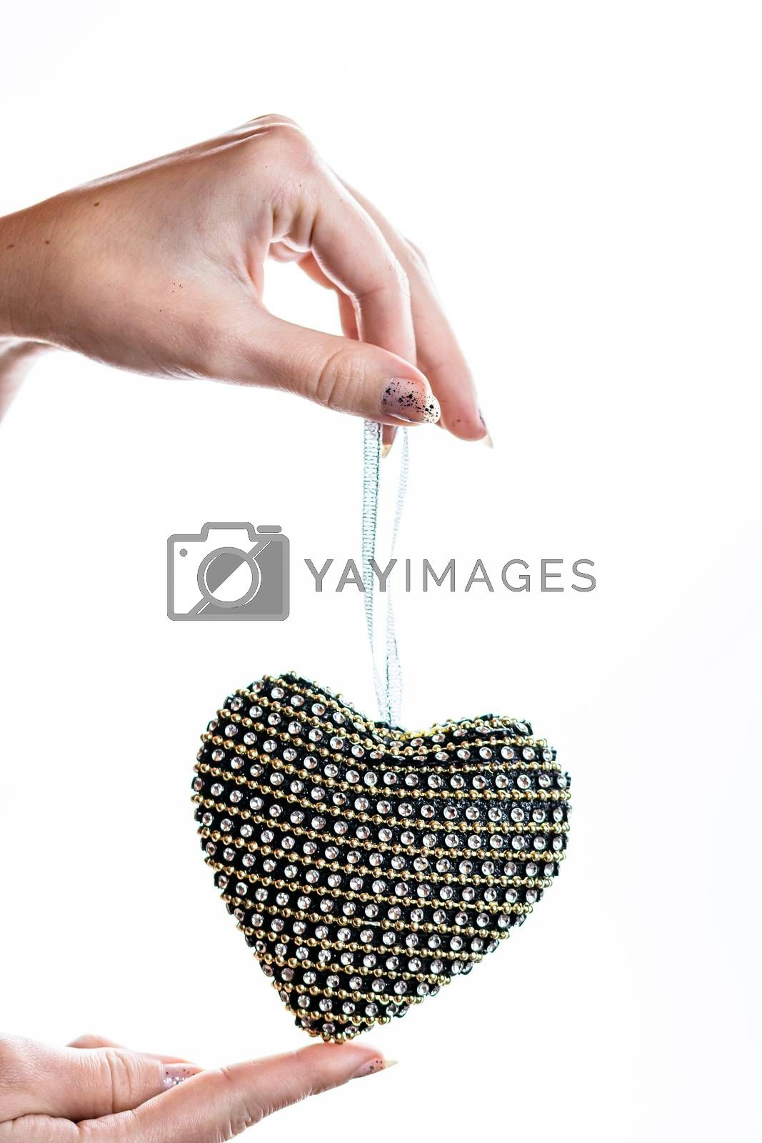Hand holding heart shaped decoration isolated on white.