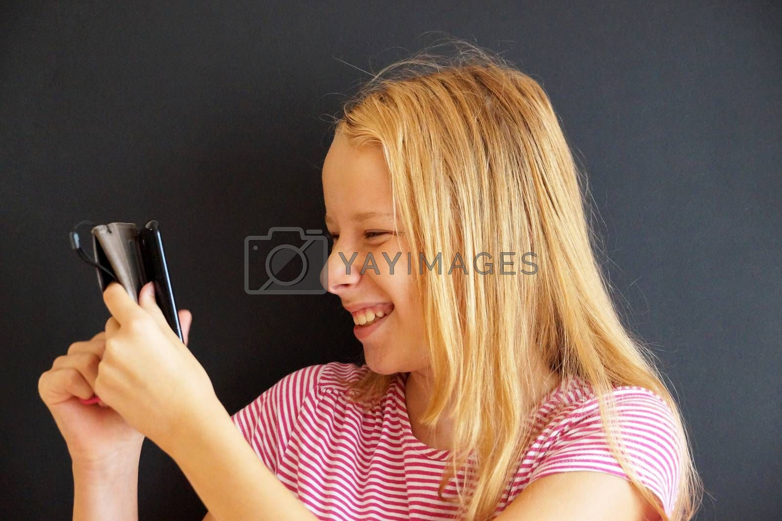 portrait of laughing teenage girl with phone on black background.