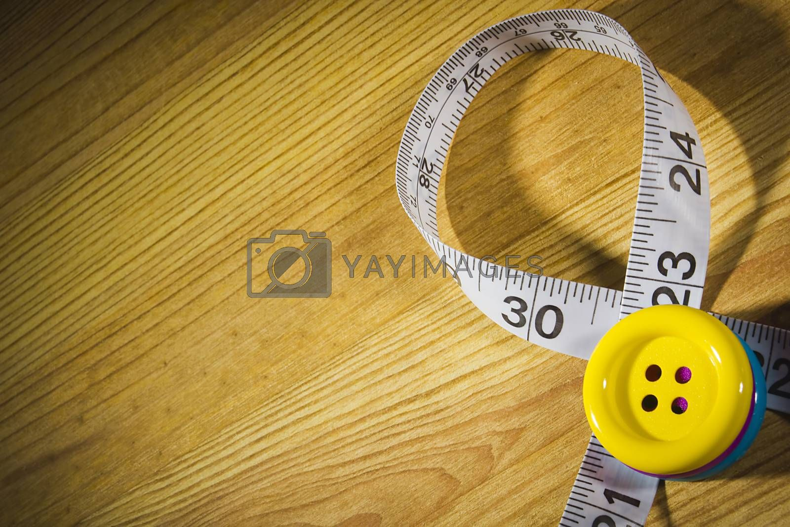 Tailor meter and buttons on wooden table