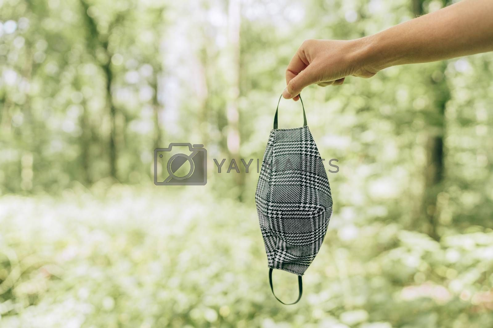 Face mask handmade with fabric in outdoor nature background. Woman holding corona protection covering in forest obligatory in public spaces.