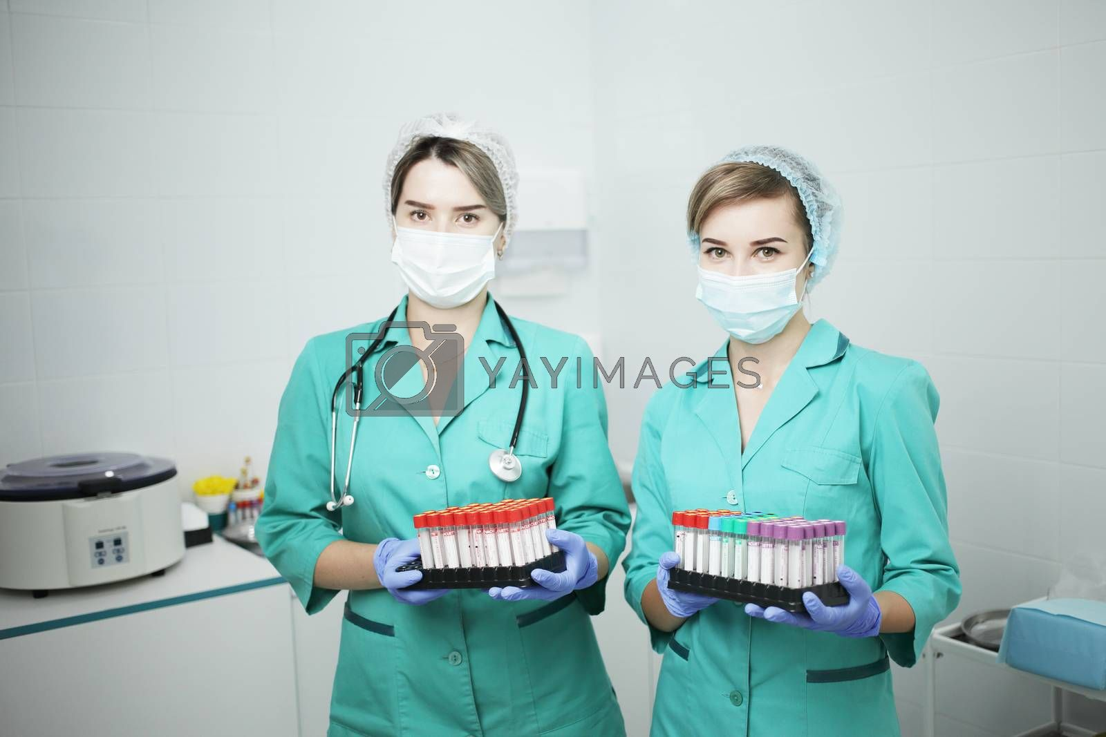 Two female nurses doctor in a hospital in a medical mask and medical clothes hold cones of a test tube for a blood test
