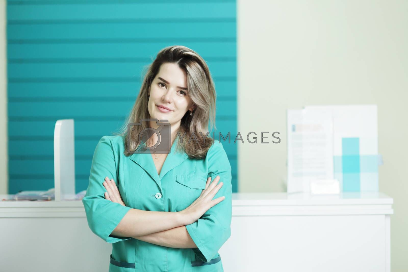 Female doctor or nurse in medical uniform looking at the camera. In the hospital reception.