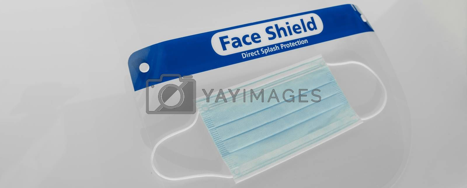 PPE for covid and corona virus. Medical mask and face shield protective equipment for healthcare workers and business. Panoramic banner crop of face covering protection by Maridav