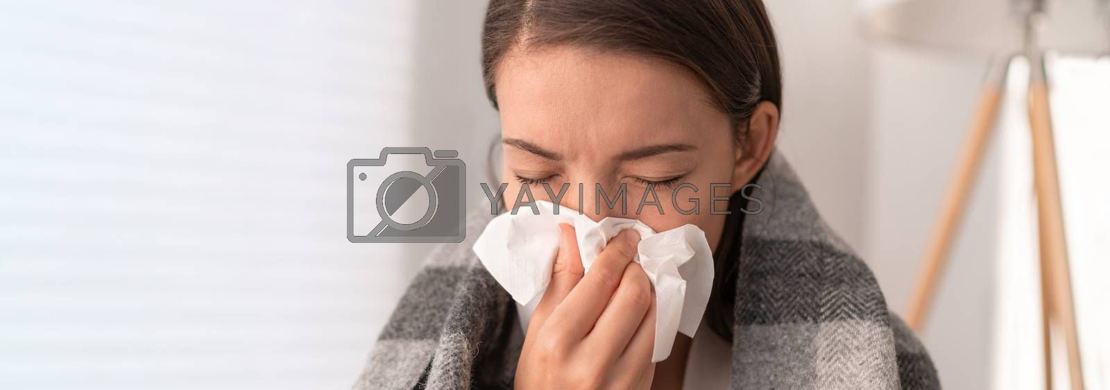 Sick woman feeling unwell staying home. Young girl with flu symptoms coughing in tissue covering nose when sneezing as COVID 19 prevention. Panoramic crop.