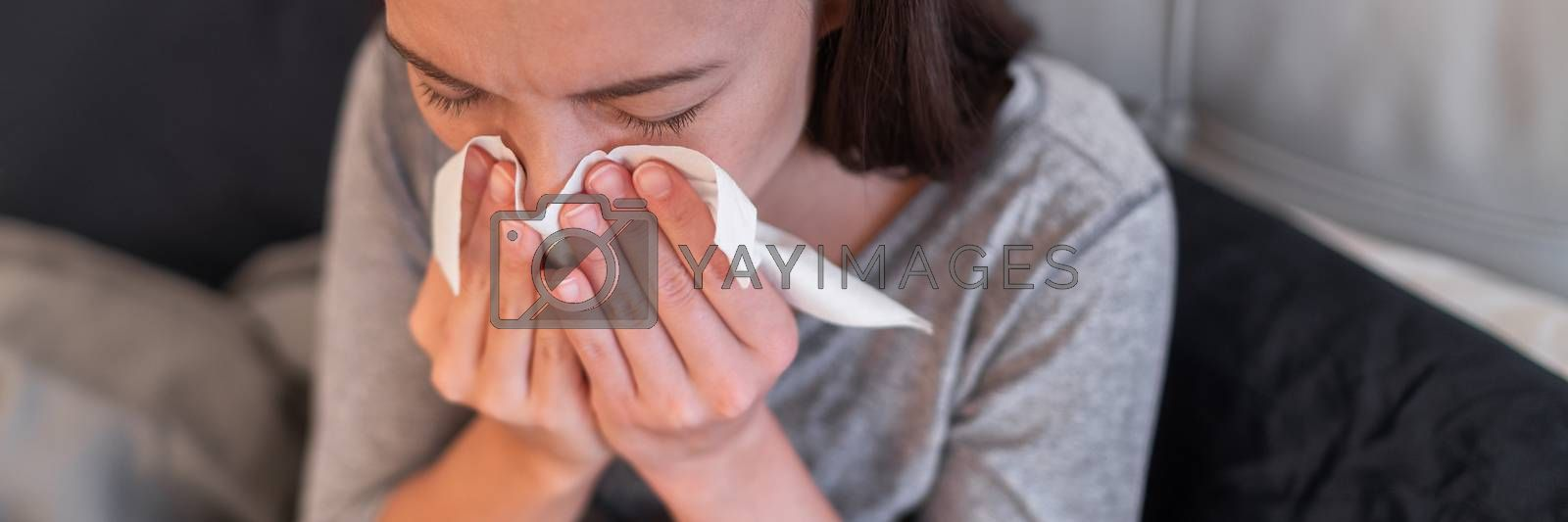 Sick woman feeling unwell at home. Young girl with flu symptoms coughing in tissue covering nose when sneezing as COVID 19 prevention. Panoramic crop by Maridav