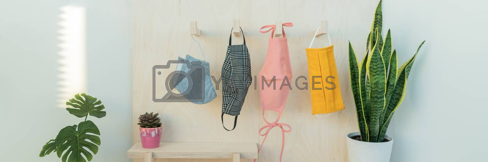 Many face masks hanging on hooks. Colorful selection of fabric colors and patterns for sale in store. Panoramic banner.