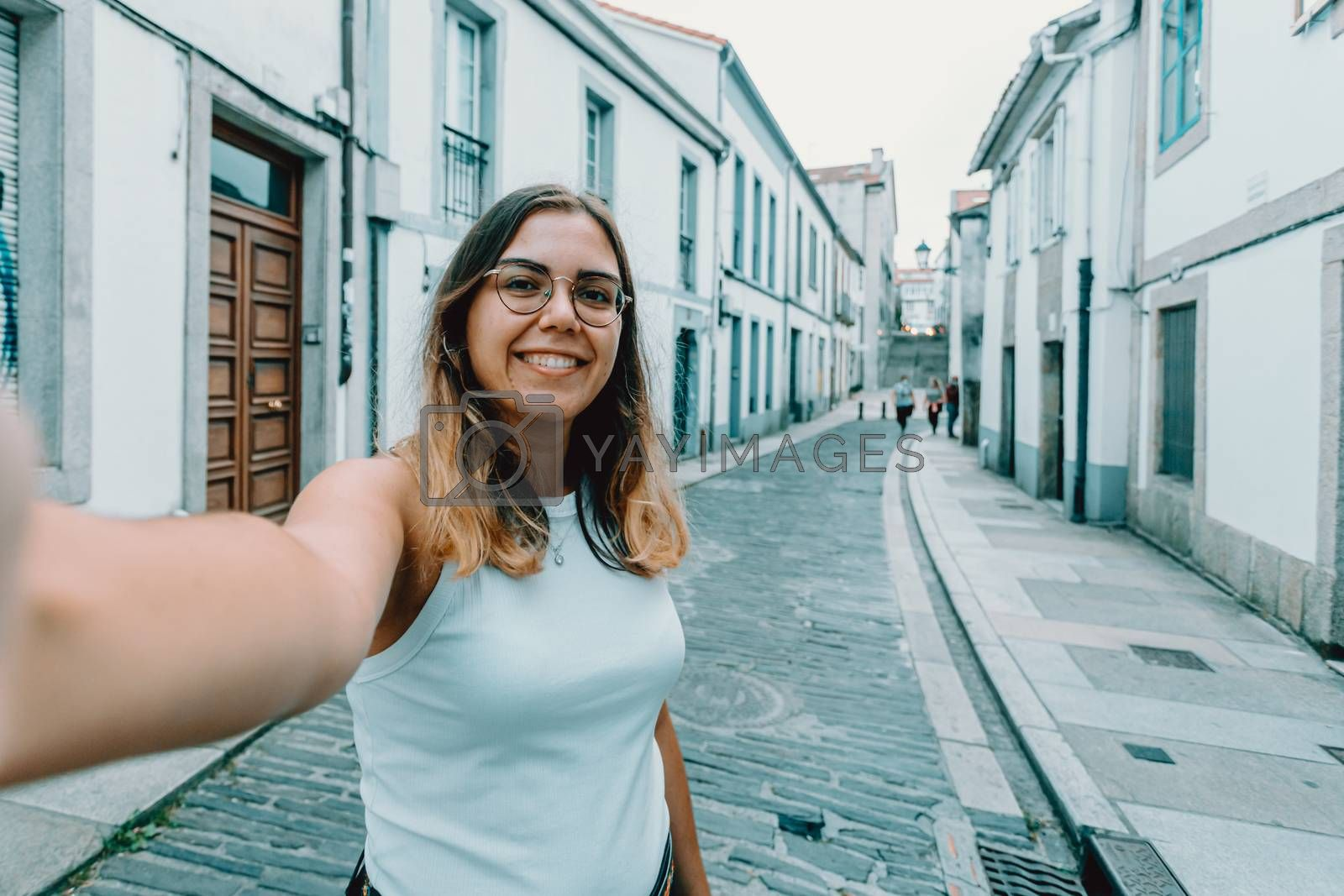 A young woman with glasses taking a selfie on a old spanish street
