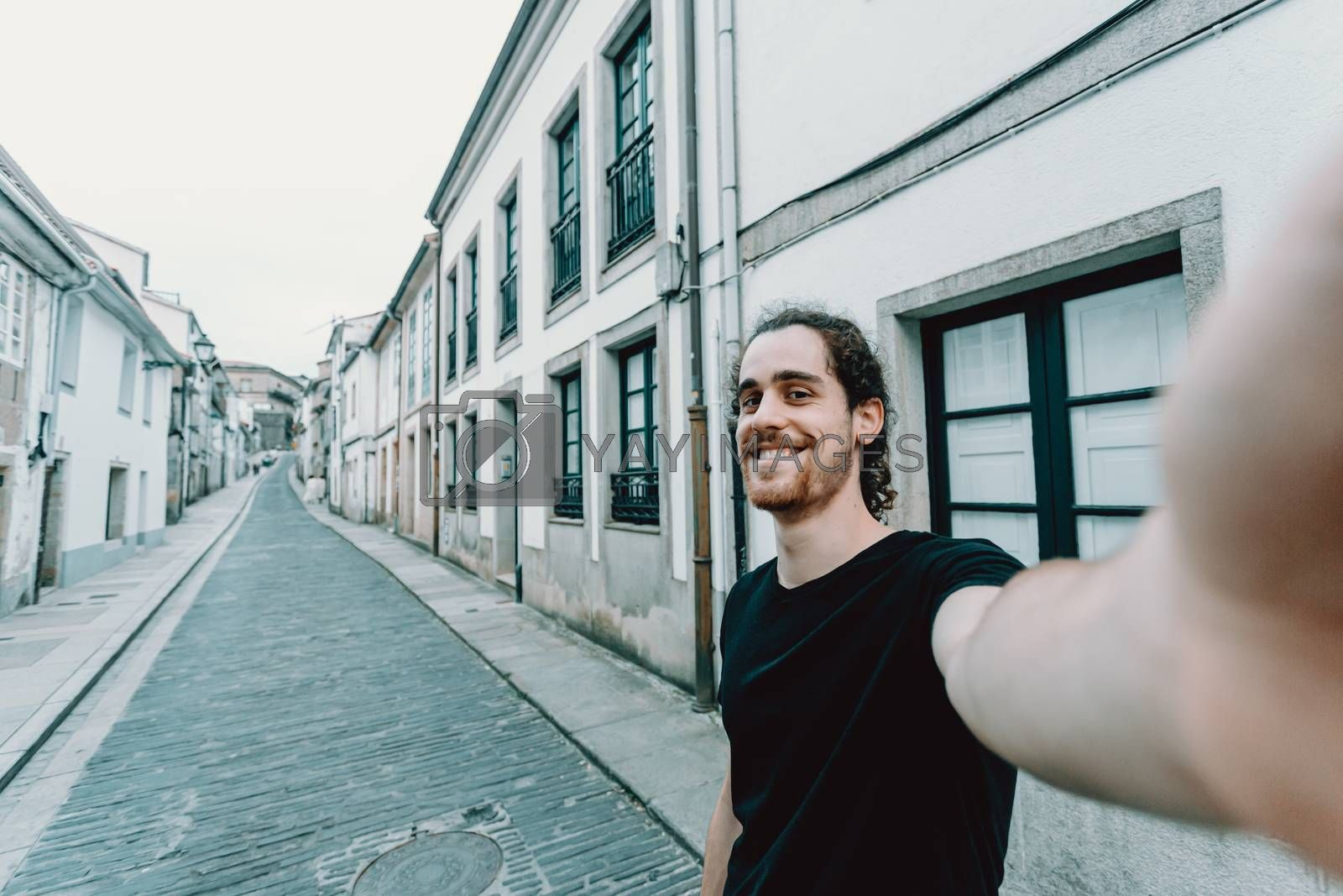 A young man with glasses taking a selfie on a old spanish street