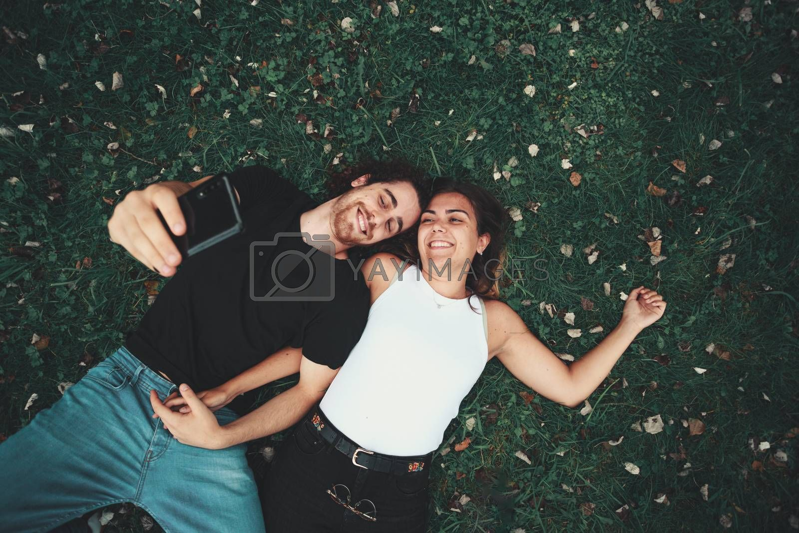 A young couple taking a selfie while lying on the grass