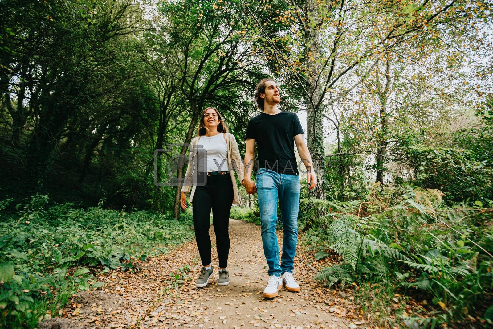 A front view of a young couple taking a walk and exploring the forest