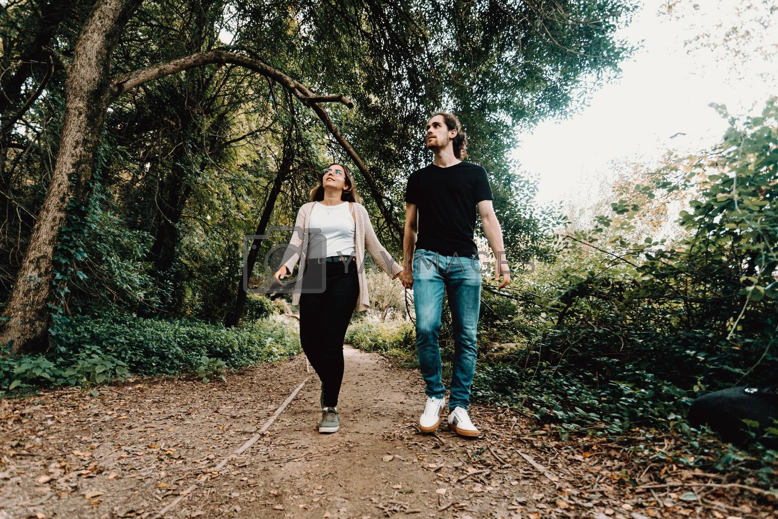 A front view of a young couple taking a walk and exploring the forest during autumn