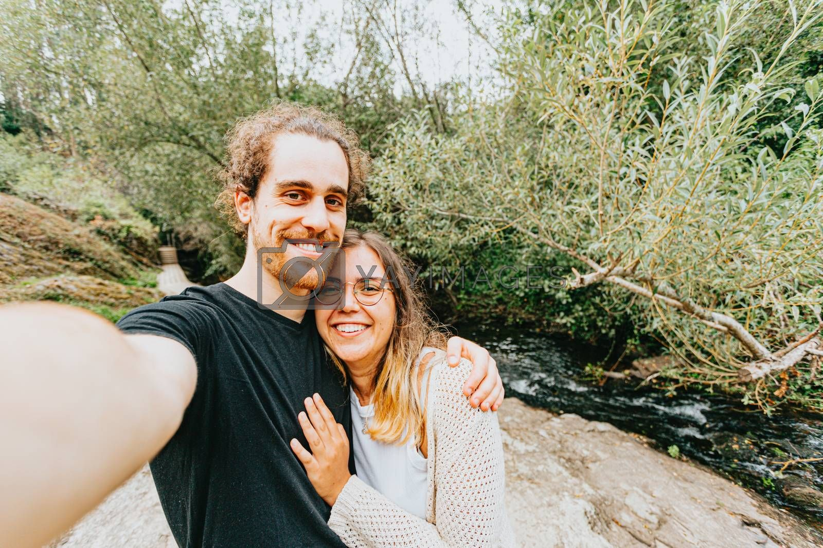 A young spanish couple taking a lovely selfie in the shore of a river