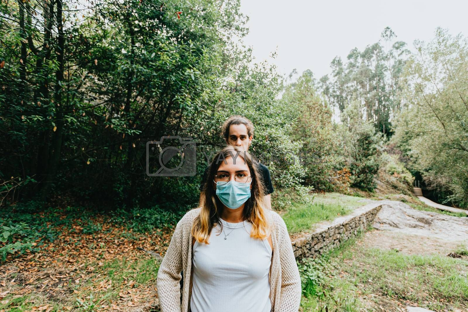 A front shot of a serious couple with the masks put on in the forest