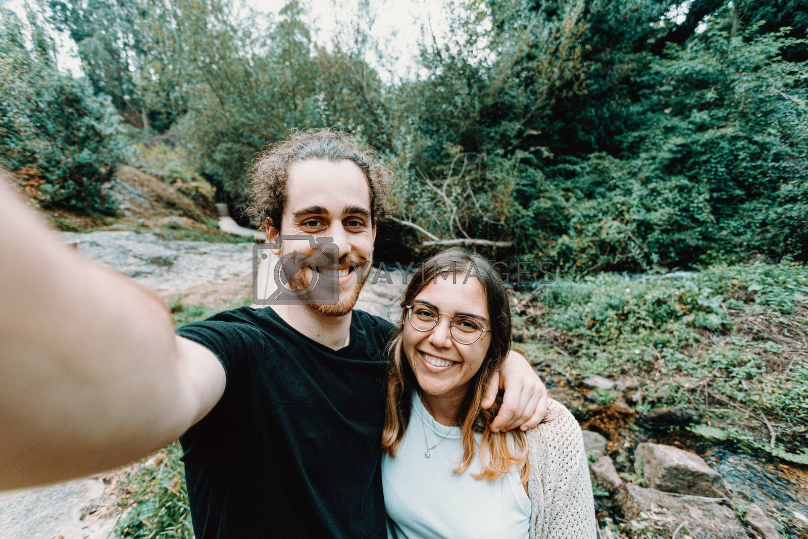 A selfie of a young couple giving a bis smile to the camera on the forest